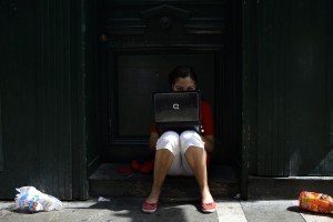 DOCU_GRUPO A girl wearing the traditional red and white festival costume uses a laptop computer on the first day of the San Fermin Festival in Pamplona